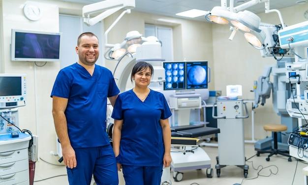 Man en vrouw arts staan in de operatiekamer. moderne medische en chirurgische apparatuur op de achtergrond.