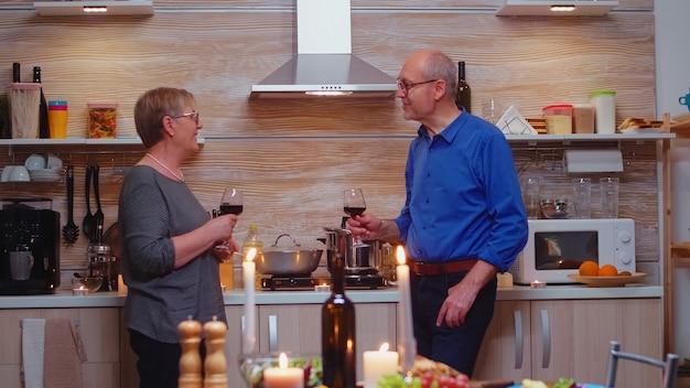 Man en vrouw bespreken grappige dingen na een romantisch diner. senior oud stel dat wijn drinkt en praat, in de buurt van de keukentafel zit en hun jubileum viert in de eetkamer.