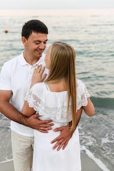 Man en vrouw bij een romantische zonsondergang van de dag bij de zee. geliefden rennen langs het strand. huwelijksreis voor de pasgetrouwden.