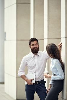 Man en vrouw buiten chatten tijdens koffiepauze