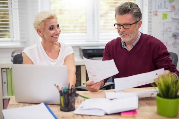 Man en vrouw die achter het bureau werken