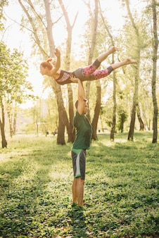 Man en vrouw die acroyoga in tuin uitoefenen