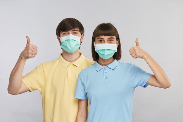 Man en vrouw die ademhalingsmaskers in gele en blauwe shirts dragen die duimen omhoog gebaar, gelukkige en gezonde mensen tonen terwijl coronavirus