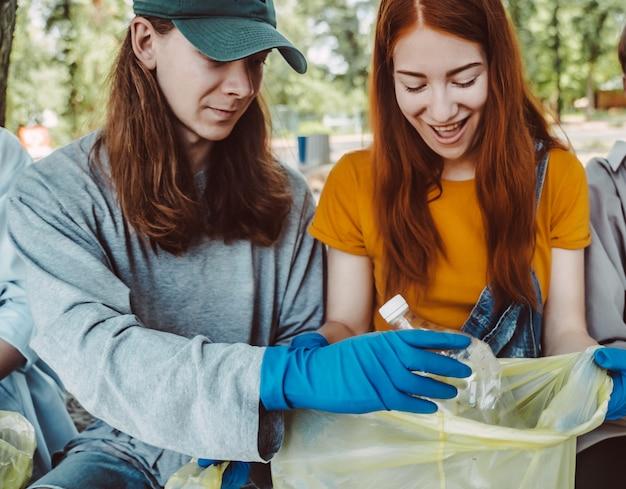 Man en vrouw die afval van het park opnemen. ze verzamelen het afval in een vuilniszak