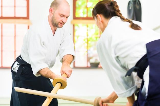 Man en vrouw die aikido-zwaardstrijd hebben