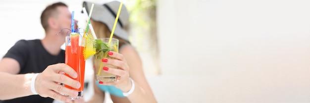 Man en vrouw die alcoholische cocktails houden en kussen. romantisch reizen en romantische dates concept