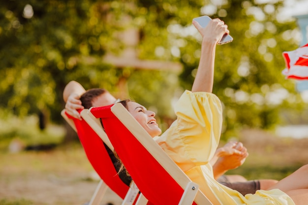 Man en vrouw die bij rode strandstoelen liggen en selfie maken via de telefoon