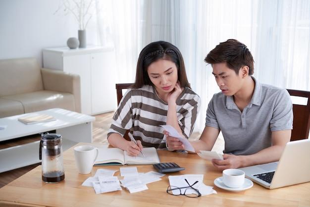 Man en vrouw die binnenlandse begroting thuis berekenen