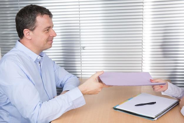 Man en vrouw die contract of document ruilen