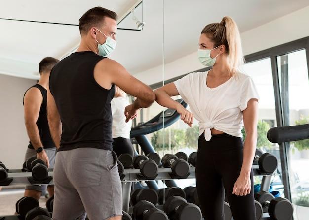 Man en vrouw die de ellebooggroet geven in de sportschool
