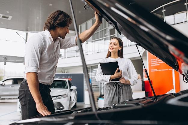 Man en vrouw die een auto in een autotoonzaal kiezen