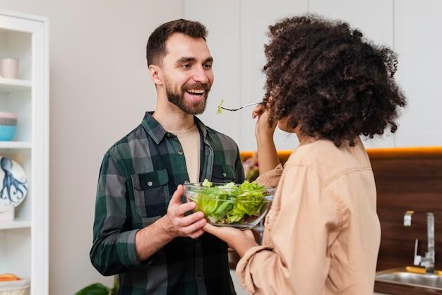 Man en vrouw die een kom salade houden