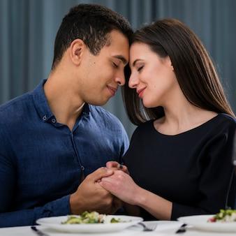 Man en vrouw die een romantisch valentijnsdagdiner hebben binnen