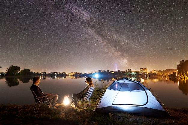 Man en vrouw die een rust op kust hebben onder nachthemel