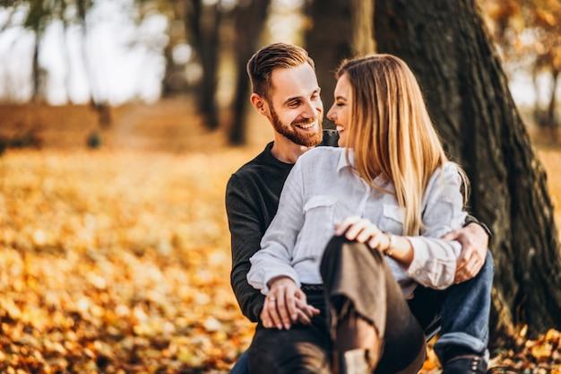 Man en vrouw die en in herfstpark koesteren glimlachen