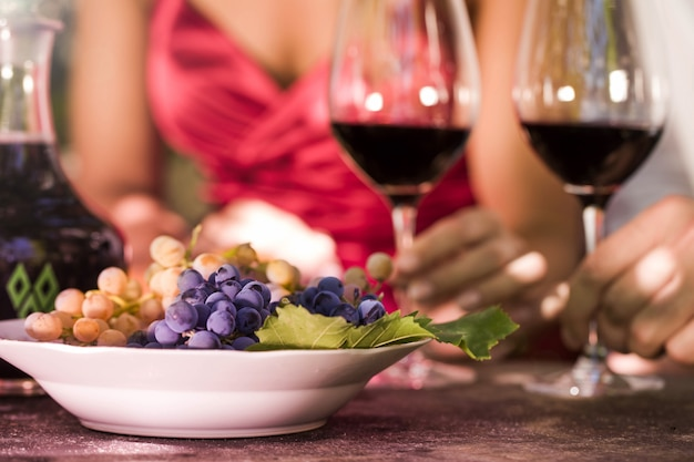 Man en vrouw die gelezen wijn drinken en druiven eten
