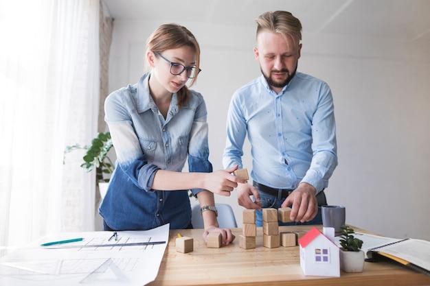 Man en vrouw die houten blok op werkend bureau stapelen op kantoor