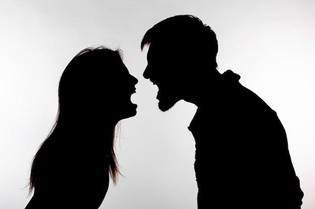 Man en vrouw die huiselijk geweld uiten in studio silhouet