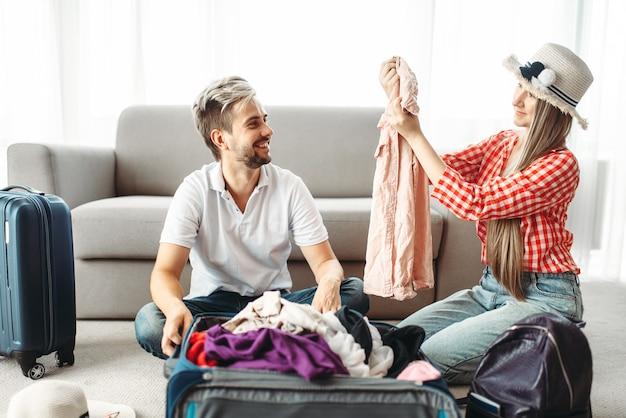 Man en vrouw die hun koffers inpakken voor vakantie