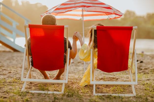 Man en vrouw die in de zomerkleren bij rode strandstoelen op zandstrand leggen terwijl zonsondergang. de focus ligt bij handen. uitzicht vanaf de achterkant.