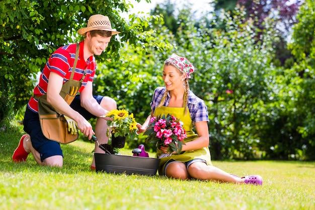 Man en vrouw die in tuin bloemen planten