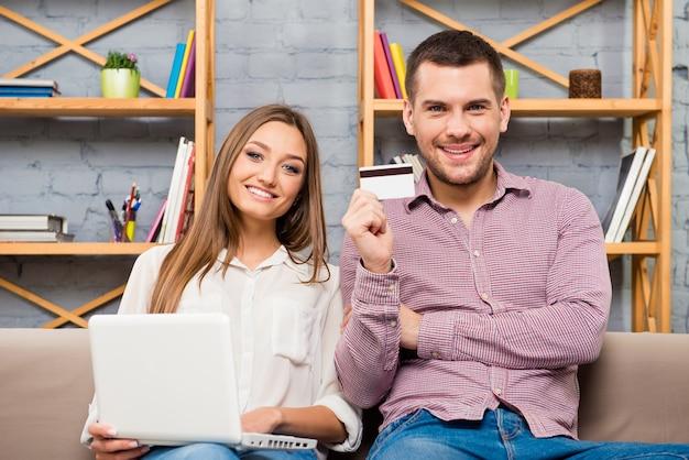 Man en vrouw die internet winkelen met laptop en bankkaart maken