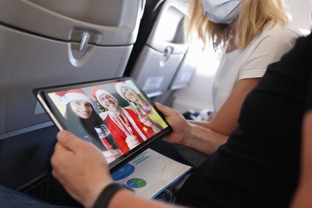 Man en vrouw die kerstmis vieren met vrienden in santa claus-hoeden via het scherm op digitale tablet in de close-up van de vliegtuigcabine
