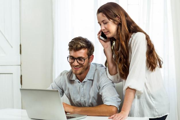 Man en vrouw die laptop en mobiele telefoon in bureau met behulp van