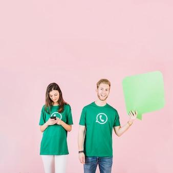 Man en vrouw die lege toespraakbel en smartphone houden