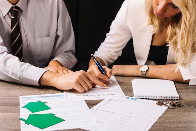 Man en vrouw die leningsdocumenten ondertekenen