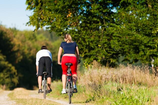 Man en vrouw die met fiets uitoefenen
