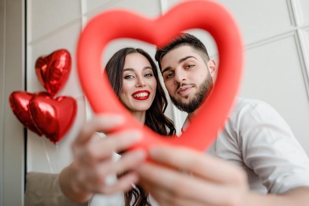 Man en vrouw die met hartvorm in handen door thuis met ballons kijken