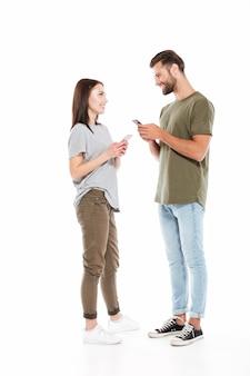 Man en vrouw die met smartphones elkaar bekijken