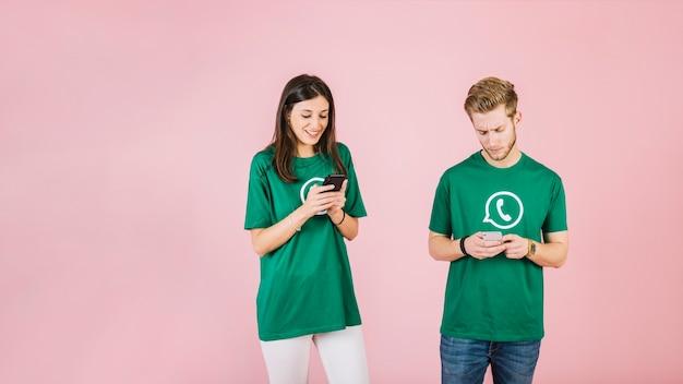 Man en vrouw die mobiele telefoon op roze achtergrond met behulp van