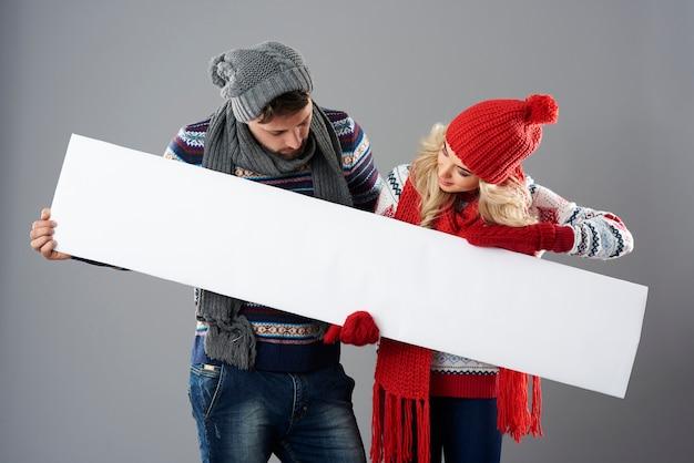 Man en vrouw die neer op witte banner kijken