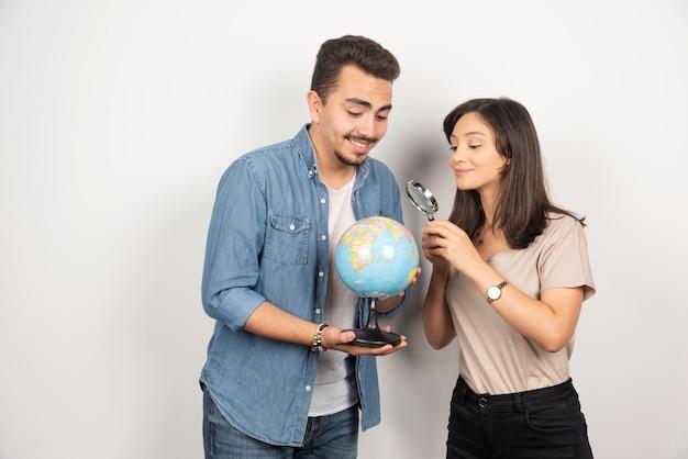 Man en vrouw die op bol op wit kijken.