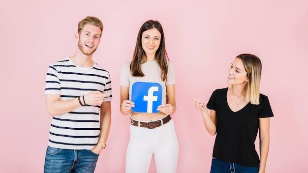 Man en vrouw die op hun facebookpictogram van de vriendenholding op roze achtergrond richten