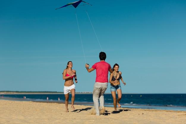 Man en vrouw die op strand met vlieger lopen
