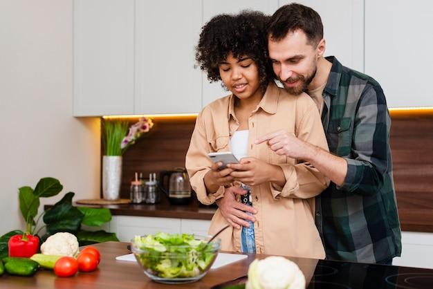 Man en vrouw die op telefoon in keuken kijken