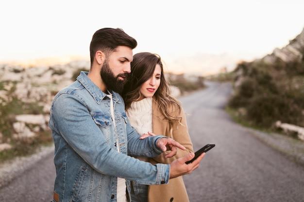 Man en vrouw die op telefoon op weg kijken