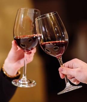 Man en vrouw die rode wijn drinken. op de foto, close-up handen met een bril.