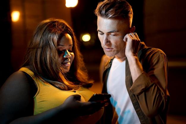 Man en vrouw die 's nachts smartphone gebruiken in de stadslichten