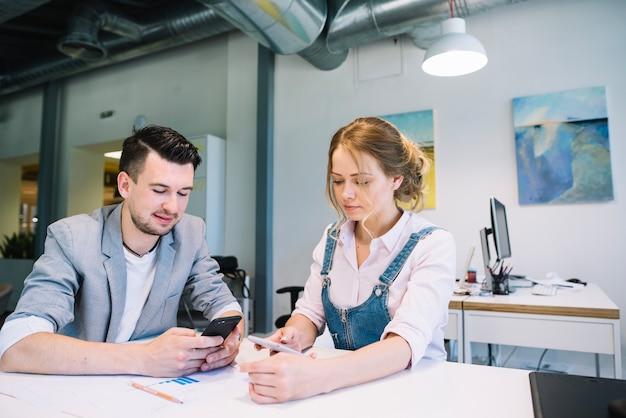 Man en vrouw die smartphones in bureau gebruiken