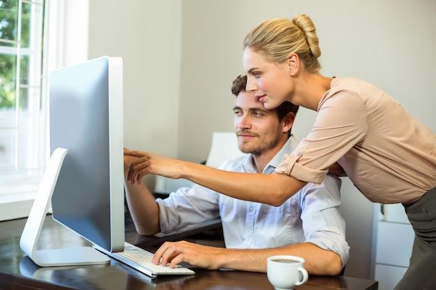 Man en vrouw die terwijl het werken aan computer op kantoor bespreken