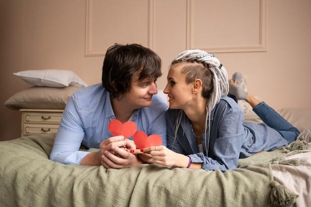 Man en vrouw die thuis elkaar met rood hartvalentijnskaart in handen bekijken.
