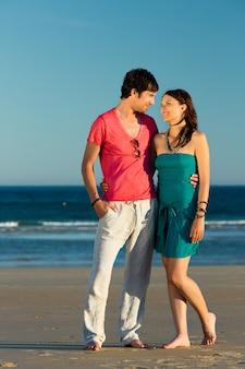 Man en vrouw die van zonsondergang op strand genieten
