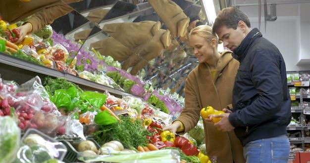 Man en vrouw die verse groenten in supermarkt kopen