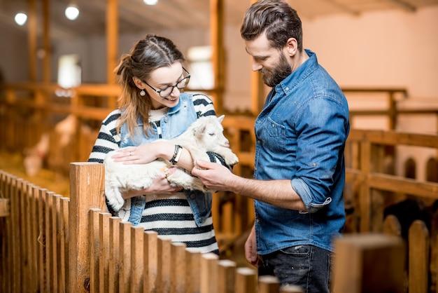 Man en vrouw dierenartsen zorgen voor kleine babygeiten binnenshuis in de schuur