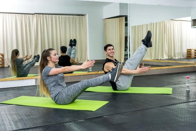 Man en vrouw doen oefeningen zittend op de vloer