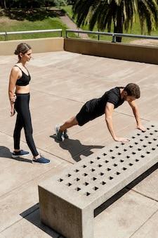 Man en vrouw doen push-ups buitenshuis
